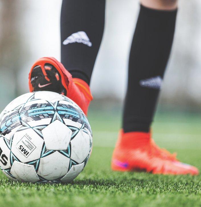 Närbild på fotboll med elev som lutar sin fot på bollen