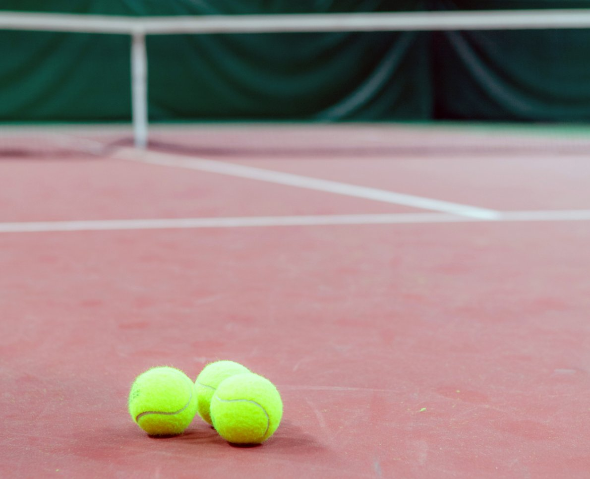Tre tennisbollar ligger på en tennisplan
