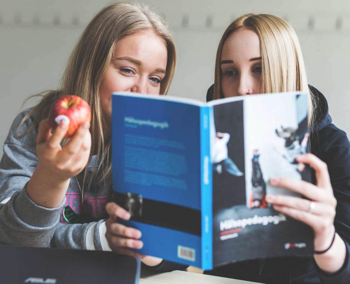 Eleve inspekterar bok och en håller upp ett äpple